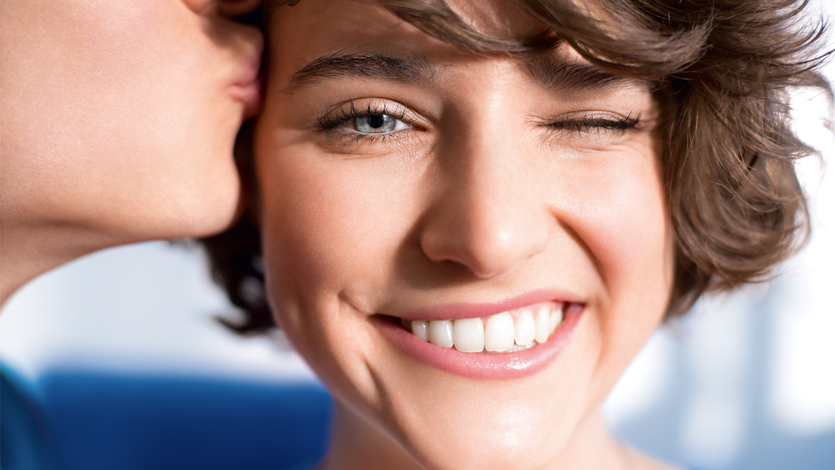 Smiling, brown-haired woman winking and being kissed on the temple.